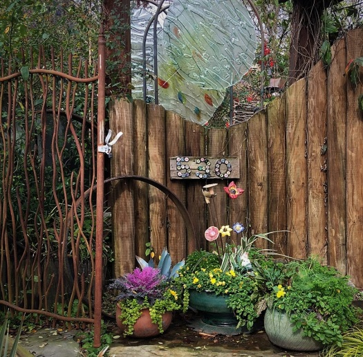 Felderyard entry with artisan gate, glass sculpture., and ceramic flowers
